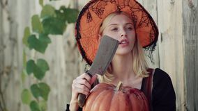 Halloween girl. Halloween woman posing with pumpkin. Glamour fashion vampire lady with witch costume. Beautiful young stock video footage