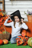 Halloween girl. Girl in hat of witch and  orange pumpkins Stock Photos