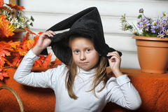 Halloween girl. Girl in hat of witch and  orange pumpkins Royalty Free Stock Photos