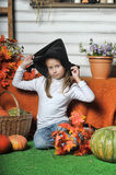 Halloween girl. Girl in hat of witch and  orange pumpkins Royalty Free Stock Photo
