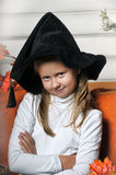 Halloween girl. Girl in hat of witch and  orange pumpkins Stock Photography