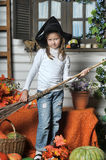 Halloween girl. Girl in hat of witch and  orange pumpkins Royalty Free Stock Image