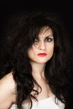 Halloween girl. Portrait of black-haired woman with disheveled hair and ruby lipstick on black background Stock Photo