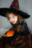 Halloween. Girl portray evil sorceress. She is wearing black-and-orange dress and hat. From under his hat sticking disheveled hair. Girl has an evil expression Stock Image