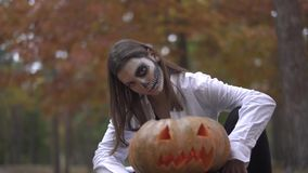 Halloween. A girl with a scary Halloween makeup is sitting near the pumpkin. A girl with a scary Halloween makeup is sitting near the pumpkin. Halloween holiday stock video footage