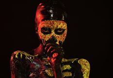 Halloween girl with skull face paint on black background. Life and death concept. Day of dead celebration. Body painting and art. Woman skeleton with flower on royalty free stock photo