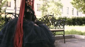 Halloween girl in witch sitting on a bench in the city park forest. Mystery and horror concept. stock footage