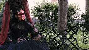 Halloween girl in witch sitting on a bench in the city park forest. Mystery and horror concept. stock video footage