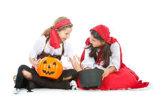Halloween: Girls Sharing Halloween Candy. Halloween series with cute children dressed as Dracula, a pirate, and Little Red Riding Hood.  Isolated on white Royalty Free Stock Photo
