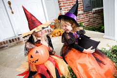 Halloween: Girls Sit On Front Porch With Trick Or Treat Candy Stock Photography