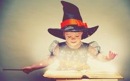 halloween gladlynt liten häxa med en trollspö och ett glödande b Royaltyfri Foto