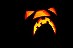 Halloween glowing pumpkin face. Only the glowing evil face of a Halloween pumkin is shown in front of a black background. A maggot crawls near the left side of Stock Photos