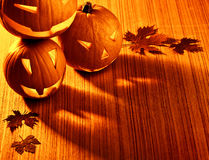 Halloween glowing pumpkins border. Picture of halloween glowing pumpkins border, three orange carved pumpkins and old dry leaves on wooden background, scary Stock Photography