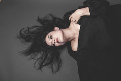 Halloween, gothic dark woman with large black cloth on gray back Royalty Free Stock Photos