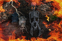 Halloween Graveyard. Skeletons and tombstones in dirt with flames and lightning Royalty Free Stock Image