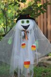 Halloween green-eyed ghost decoration. Silly white faced hat-wearing veiled green-eyed smiling ghost doll patio decoration for Halloween for the home Stock Images