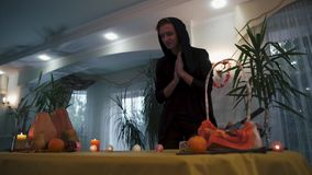 Halloween. Magician in the black overalls comes to the festive table. stock footage