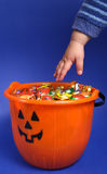 Halloween Hand. A child's hand reaching into a pumpkin themed bucket filled with colorfully wrapped chocolate candy Stock Images