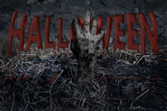 Halloween. The hands of the zombies emerge from the grave and squeezed the words Halloween until blood flowed to the ground Stock Photos
