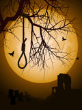 Halloween hangmans noose. Hangmans noose hanging from a bare tree against a full moon with abbey and grave yard in background Stock Photo