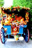 Halloween Harvest. A festive Halloween harvest cart stuffed with fall flowers and pumpkins Royalty Free Stock Photo