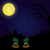 Halloween. A haunted graveyard with a pair of zombie's hands, a tree and some tombs Royalty Free Stock Photo
