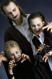 Halloween haunting. Father with children dressed up as vampires and making angry faces Royalty Free Stock Image