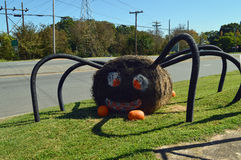 Halloween Hay Bale Spider and Pumpkins. Halloween display that looks like a big black spider made from a round hale bale painted black with pumpkins Stock Photography