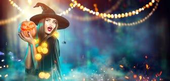 Halloween Heks met een gesneden pompoen en magische lichten royalty-vrije stock afbeelding