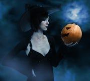 Halloween-heks met een pompoen royalty-vrije stock afbeeldingen