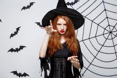 Halloween-heksenconcept - Halloween-Heks het gieten werktijden de Van gemiddelde lengte met ernstige uitdrukking over donkere gri Stock Afbeeldingen