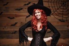 Halloween-heksenconcept - het Gelukkige de holding van de het haarheks van Halloween rode stellen over oude houten studioachtergr Stock Afbeelding