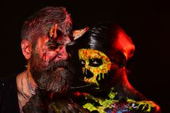 Halloween hell, death, life, evil concept. Satan hipster and girl skeleton on black background. Trick or treat. Cosplay couple, holiday celebration. Woman with royalty free stock photo