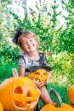 Halloween Het kind gekleed in zwarte met in hand hefboom-o-lantaarn, de truc of behandelen Gelukkige meisjepompoen in het hout, i Stock Afbeelding