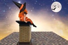 Halloween Het meisje in een zitting van het heksenkostuum op het dak en bekijkt de hemel Royalty-vrije Stock Afbeelding