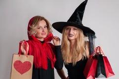 Halloween-het Winkelen De mooie meisjes in Halloween-kostuum beheksen en weinig rood berijdend hoodwitch en weinig rode berijdend Royalty-vrije Stock Afbeeldingen