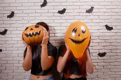 Halloween heureux ! Deux jeunes femmes mignonnes faisant la fête avec la tête de potiron Images libres de droits
