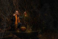 Halloween heureux ! Une jolie sorcière avec un grand potiron Beau yo image stock