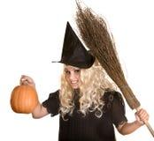 Halloween-Hexe blond im Hut und im Kürbis, Besen. Lizenzfreie Stockbilder