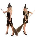 Halloween-Hexe blond im schwarzen Kleid, Hut, Besen. Stockfotografie