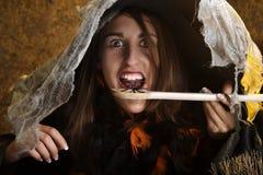 Halloween-Hexe, die eine Spinne isst Stockbilder
