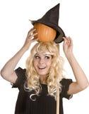 Halloween-Hexe im schwarzen Hut mit Kürbis. Stockfotos
