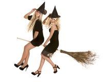 Halloween-Hexe im schwarzen Kleid und im Hut auf Besen. Stockfotos