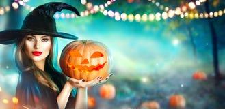 Halloween-Hexe mit einem geschnitzten Kürbis und einer Magie beleuchtet in einem Wald Stockfotos