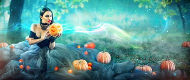 Halloween-Hexe mit einem geschnitzten Kürbis und einer Magie beleuchtet in einem Wald stockfoto