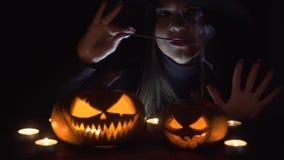 Halloween-Hexe mit einem magischen Kürbis Schöne junge Frau in den Hexen Hut und Kostümholding schnitzten Kürbis Halloween-Kunst  stock footage