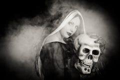Halloween-Hexe mit einem Schädel Lizenzfreies Stockfoto