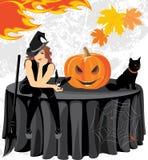 Halloween-Hexe mit einem Schläger, einer Katze und einem Kürbis, die auf dem Tisch sitzen Stockfotos