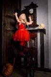 Halloween-Hexenmädchen im roten Kleid und im schwarzen Hut Lizenzfreies Stockbild