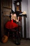 Halloween-Hexenmädchen im roten Kleid und im schwarzen Hut Lizenzfreie Stockfotos